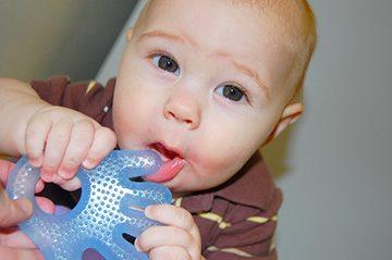 малыш пользуется прорезывателем
