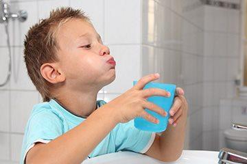 ребенок полоскает рот
